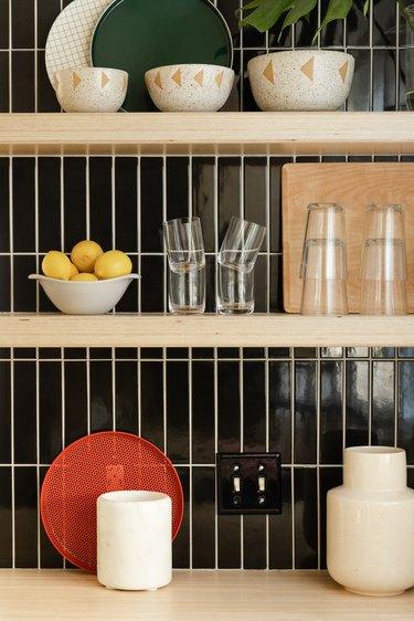 Wood kitchen shelves with dishware and black rectangular tile backsplash