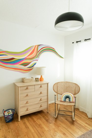 Nursery with wood floors and dresser, black bowl pendant light and colorful wall mural