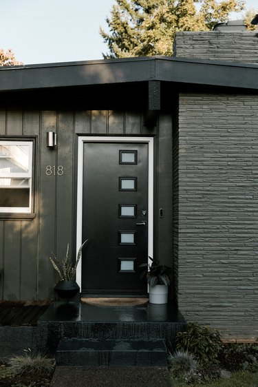 A gray and black mid-century house with a brick chimney