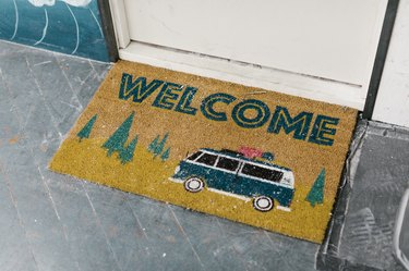 A door mat that says, 'welcome' and has an image of a camper van and trees.