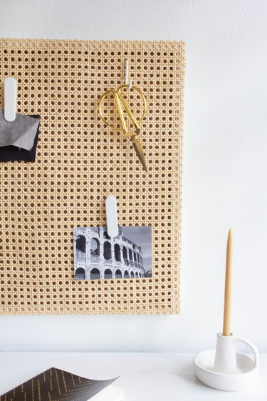 Cane memo board with scissors and photos over desk with candle