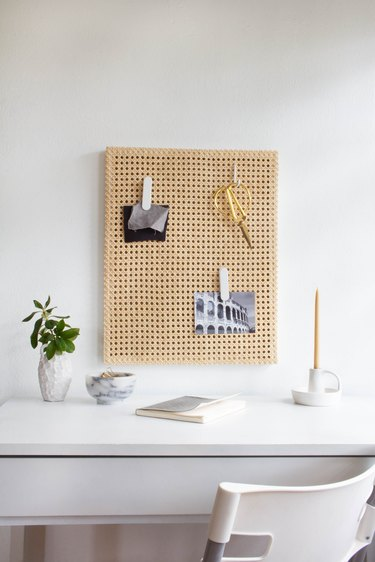 Cane memo board over white desk with plant and candle