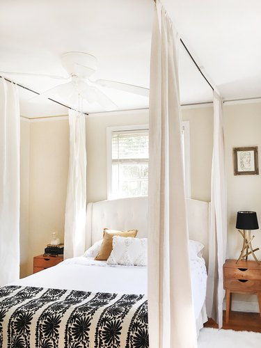 Farmhouse Chic Bedroom Ideas with a bed with curtains hanging from the ceiling around it to create a canopy
