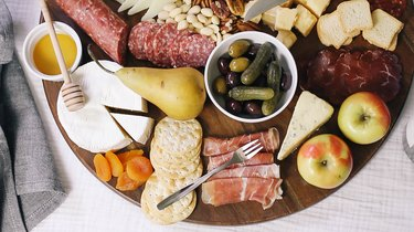 a generous charcuterie tray with meats, cheeses, fruit, nuts, and spreads