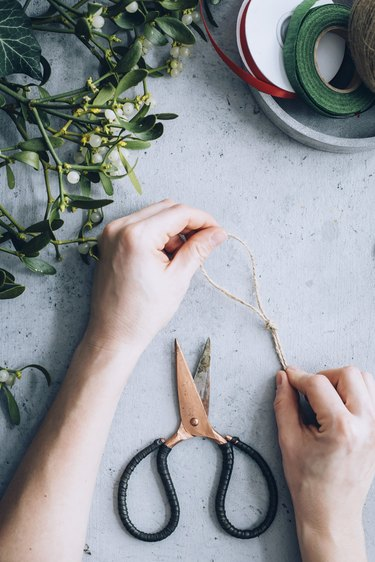 a crafter ties a piece of twine into a loop