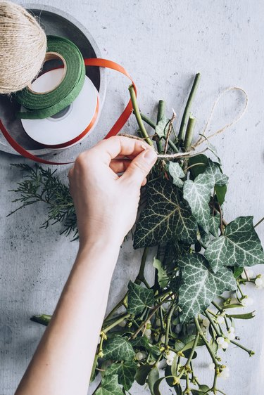 a diy bunch of mistletoe is secured with twine