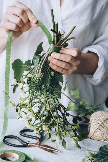 a diy bunch of mistletoe is secured with floral tape