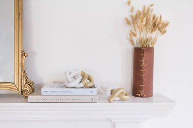 Mantel with clay knot sculptures and leather vase with dried plants