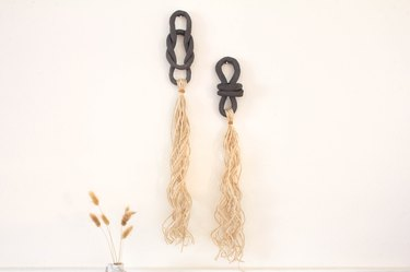 Black air dry clay with ivory jute twine on white wall next to plant