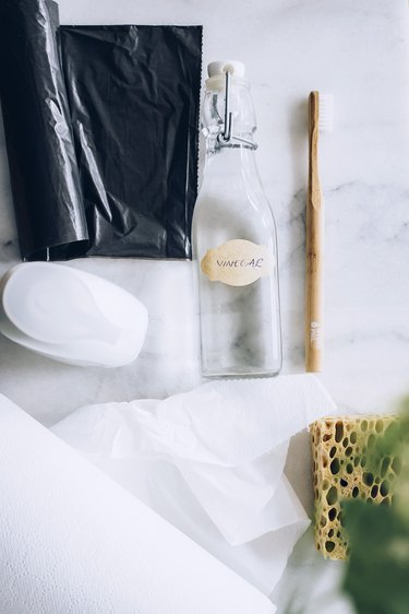 Black garbage bag, soap, empty glass bottle, wood toothbrush, paper towels, and sponger on white countertop