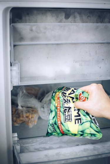 Hand removing frozen peas from freezer