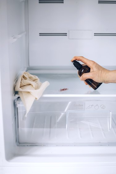 Hand using spray bottle and paper towels to clean inside shelf of white fridge