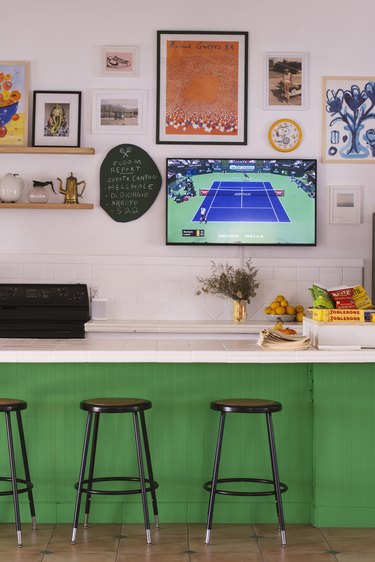 Kitchen Contemporary Bar setup with green tiled sides, white countertop, black stools, flat-screen TV, and sports parafernalia hung on pink wall