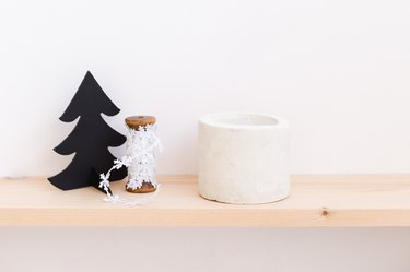 DIY concrete candle on wooden ledge next to snowflake string and Christmas tree toy against white background