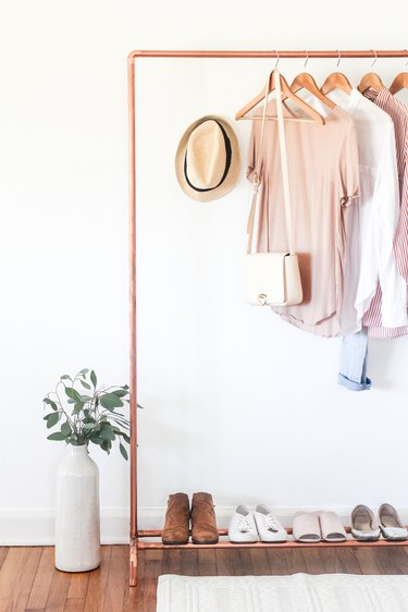 a clothing rack with a shoe rack attached made from copper pipe