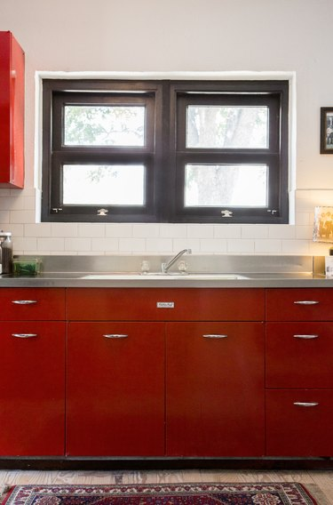 Red kitchen cabinets with a metal countertop and black window frames