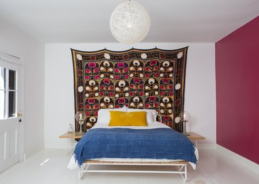 pink room ideas with Colorful bedding, a wall tapestry and globe light in a bedroom with white-pink walls