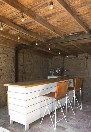 Contemporary Bar with wood counter, string lights, wood beam ceiling and industrial fan