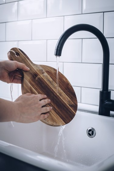 Hands washing round wood cutting board in white sink with black faucet against white tiled backsplash