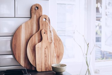 Three wood cutting boards and small cup on stone countertop leaning against tile kitchen backsplash next to white windowsill