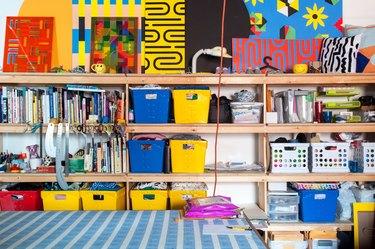 Homeschool Organization with Yellow, red, blue bins on shelves with art supplies, books, art.