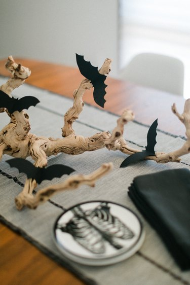 a centerpiece made from a found branch and paper bat cut-outs in the middle of a table
