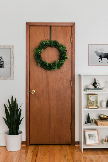 Wood door with faux evergreen Christmas wreath next to potted plant and bookshelf