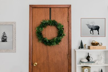 Christmas decor idea with faux evergreen wreath on wood door with framed art and white bookshelf
