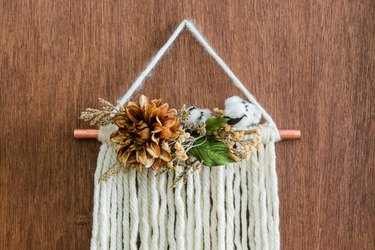 DIY fall decor idea with white yarn wall hanging with faux flowers and copper pipe