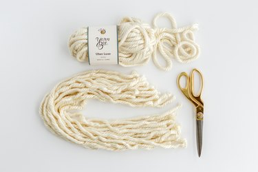 White yarn with gold scissors