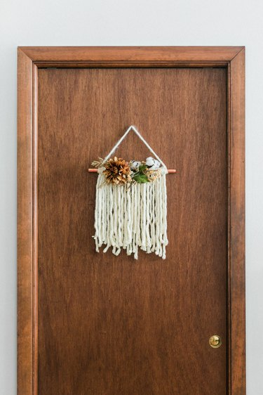Thanksgiving door hanging with white yarn and faux flowers on wood door