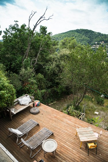 A wood deck overlooking mountains and trees with a patio furniture set