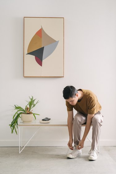 Man sitting on bench with potted plant tying shoes against white background with canvas art piece