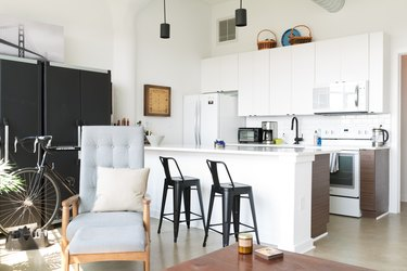 Kitchen with white cabinets, white counters, white backsplash, black chairs, and black pendant lights. A gray tufted accent chair.