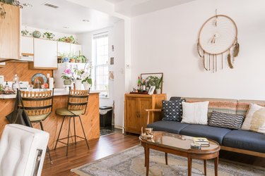 Living room with blue sofa, dreamcatcher wall hanging, bar set on a wood sideboard. Kitchen with houseplants and white-wood cabinets.