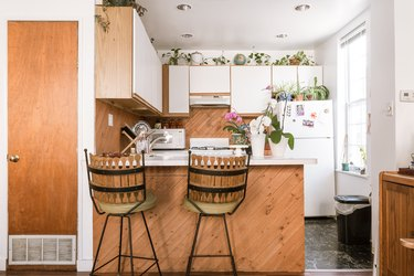 Jungalow kitchen with houseplants, wood white door cabinets, wood backsplash, marble or granite floor, and bar stools.