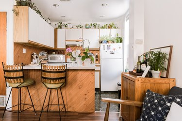 Jungalow kitchen with houseplants, wood-white door cabinets, and a kitchen island with bar stools.