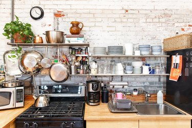 A kitchen with wood counters and white brick walls. Steel shelves with blue-white dish ware, cookware, and a plant.