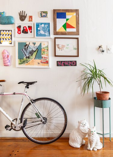 Hallway Gallery Wall Ideas with Bicycle leaning against hallway wall with artwork