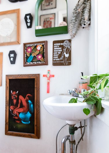 Small boho bathroom with corner sink with artwork on walls and plants on window sill