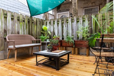 Wood deck with rattan sofa and black square table
