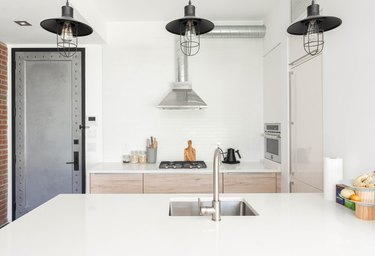 White contemporary kitchen with white countertops, wood cabinets, black stove burners, and silver sink and faucet with black hanging lights