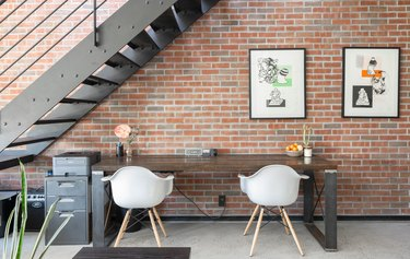 small spaces with Black metal staircase against brick wall with wood table, white curved chairs, framed print, and small metal cabinet