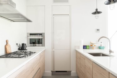 White contemporary kitchen with white countertops, wood cabinets, black stove burners, and silver sink and faucet