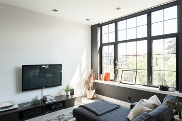 Contemporary living space with full-length windows, grey couch, entertainment center, and flat screen TV