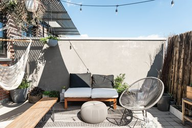 Outdoor contemporary patio with canopy, wood benches with pillows, silver metal chairs, and dried bamboo fence