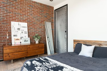 Wood cabinets with lamp, plant, and white diagram board against brick wall next to full-length mirror and black-and-white bed