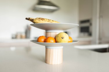 Two-tiered white and tan fruit tray with mandarins, pear, and banana on white countertop in modern kitchen