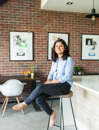 Artist sitting on wood-topped stool in brick-walled gallery space with white wood kitchen island and framed prints