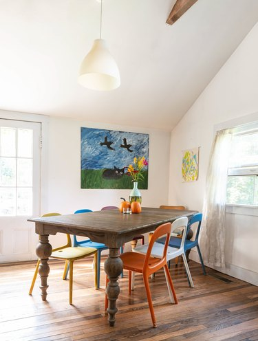 colorful metal chairs surround a rustic wood dining table